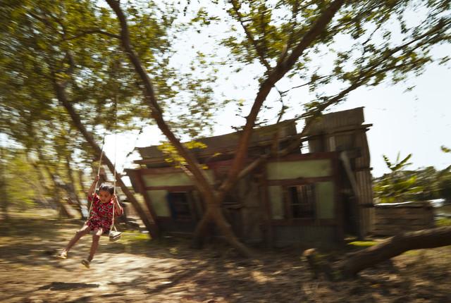 Boy playing on a swing, Bangladesh von Jakob Berr